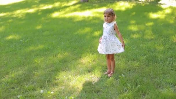 Roztomilá holčička v šatech letní smršť kolem sebe v parku.