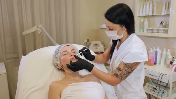 Beautician draws the contours of a white pencil on the face of the patient.