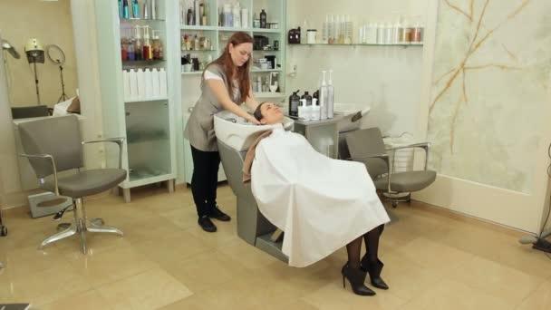 Kadeřník myje vlasy mladé dívky před účes v salonu krásy.