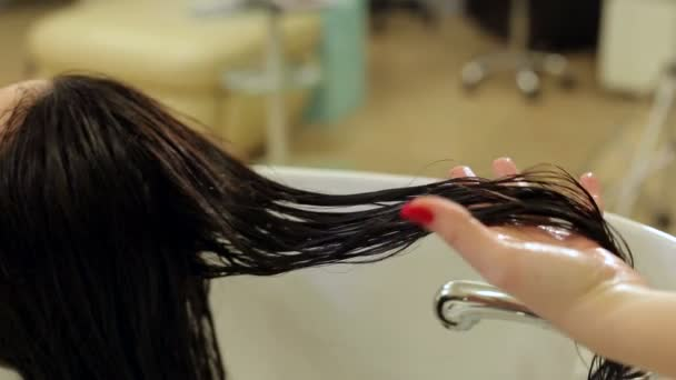 Detail kadeřník stříkající na vlhké vlasy dívka ochranným olejem. Péče o vlasy.
