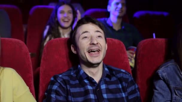 Nahaufnahme Porträt eines lachenden jungen Mannes in einem Kino.