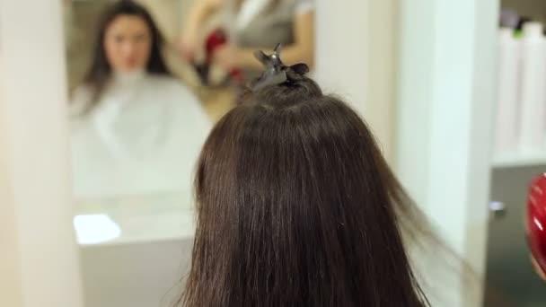 Detail kadeřník schne dlouhé tmavě hnědé vlasy v salonu krásy