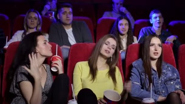 drei frustrierte junge Mädchen beim Ansehen eines uninteressanten Films im Kino.