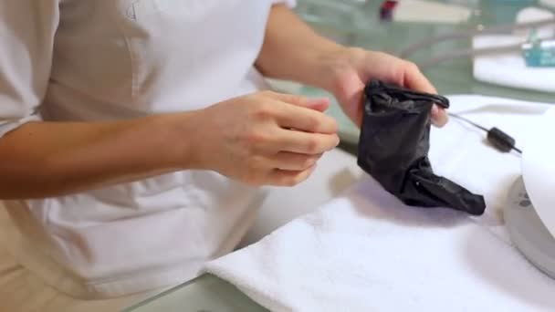 The manicure master puts on black protective gloves before manicure procedure.