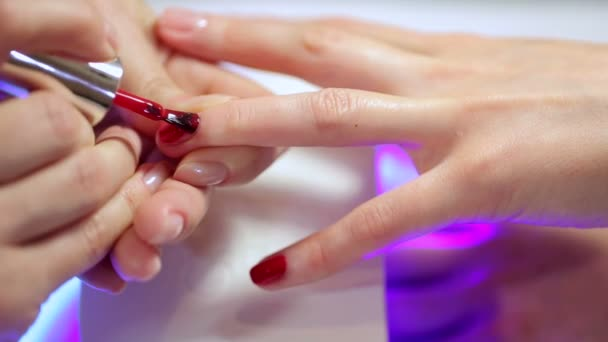 Kosmetička se vztahuje Červený lak na nehty na mladých ženách nails.