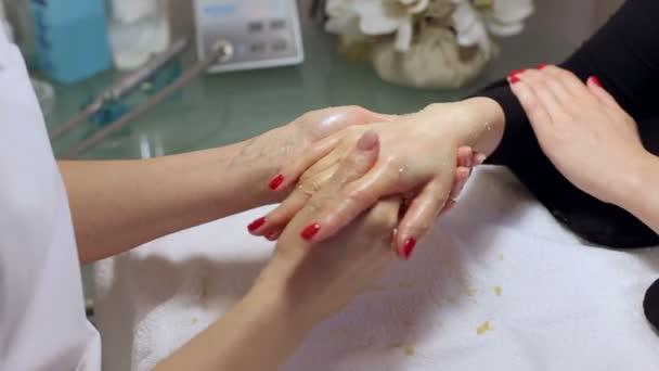 Žena ruce přijímá peeling rukou peelingu kosmetička v salonu krásy