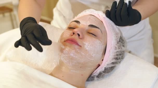 Natural sheet mask for the face skin care. Young woman at the spa salon.