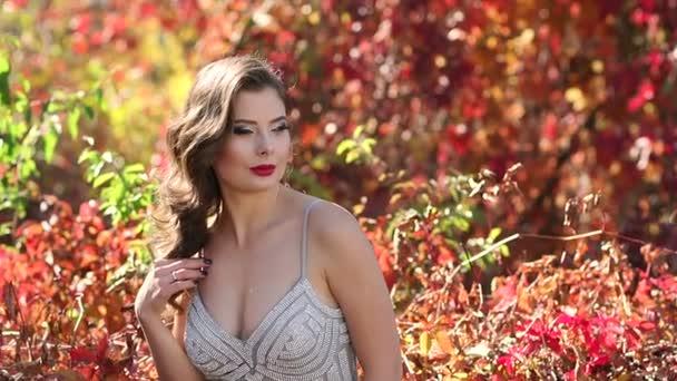 Sexy dívka ve večerních šatech chodí v podzimním parku v teplém počasí.