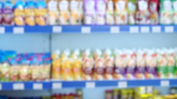 Abstraktní rozmazané supermarket s různými produkty na policích.