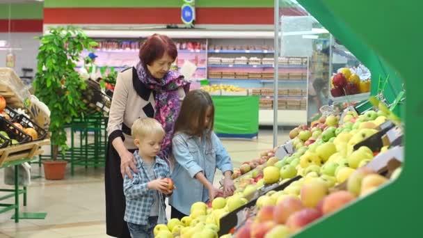 Šťastná starší žena s vnoučaty v supermarketu kupuje ovoce.