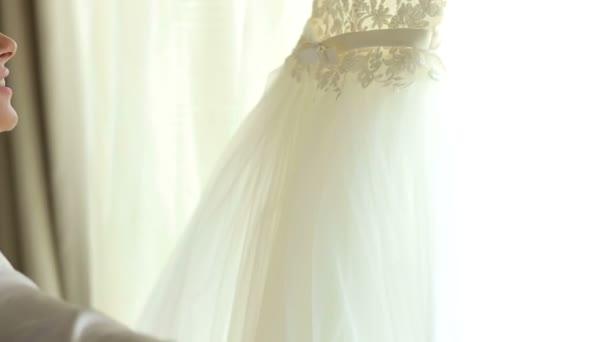 Menyasszony, megcsodálta az ablak előtt esküvői ruháját selyem köntös.