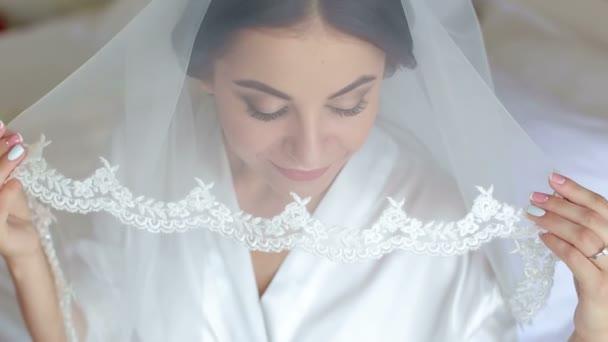 Gyönyörű nő szerzés kész részére esküvője napján, tartja a fátylat, és mosolyogva.