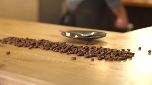 Detail z kávových zrn na dřevěný stůl v kavárně.