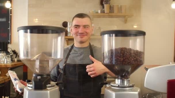 Lächeln glücklicher Mann Barista zeigt Daumen nach oben Geste im Restaurant stehen.