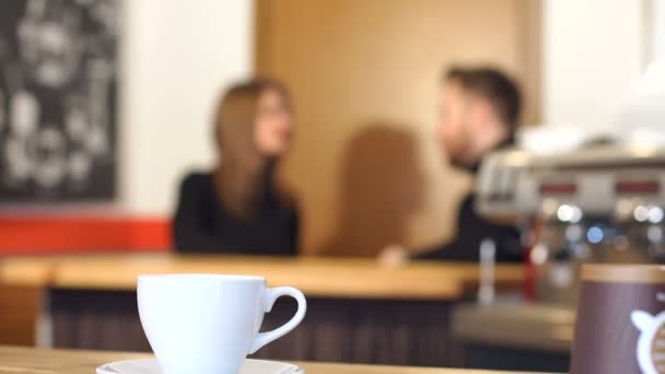 The cup of coffee on the background of the couple in the cofee shop.