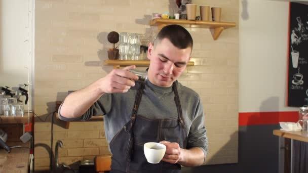 Ember Barista öntenek egy csésze kávé fahéj egy modern kávézó.