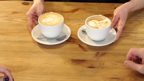 Barista holding two aromatic cappuccino, serving them to coffee shop visitors.
