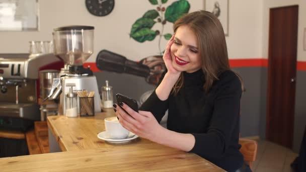 Portré egy fiatal lány egy kávézóban a latte és a telefon a kezében.