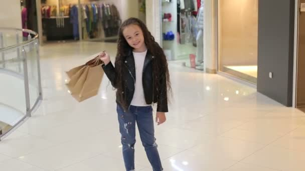 Portrét malé dívky s dlouhými kudrnatými vlasy v nákupním středisku s balíčky