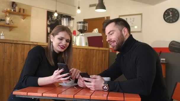 Beautiful smiling woman and handsome man drinking coffee and using mobile phone.