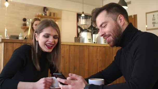 A young cheerful couple rest in a coffee shop and look at the phone screens.
