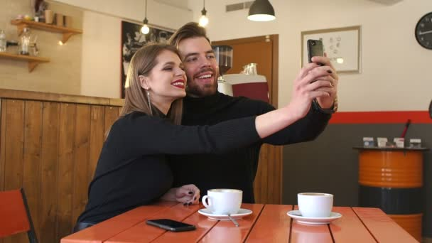 Happy couple sitting in the cafe and taking a selfie.