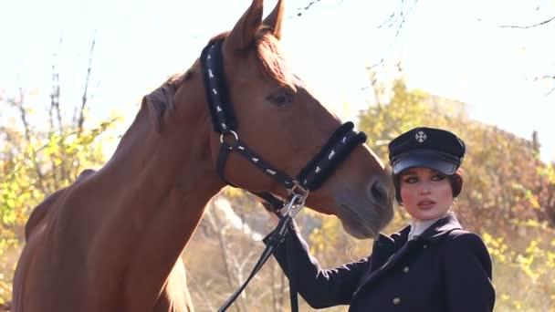 Barna ló őszén különleges ruhát és kalapot gyönyörű lány portréja