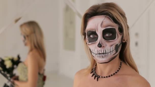 Mädchen im Kleid mit einem Blumenstrauß und Make-up in Form von Skelett