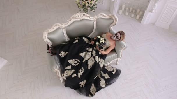 Eine gruselige Frau in einem Kleid und mit Make-up in Form eines Schädels liegt auf Retro-Sofa