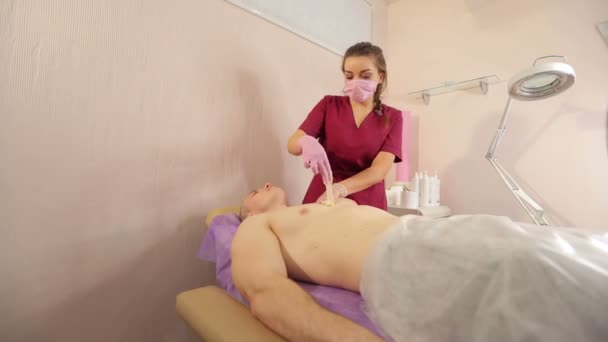 Beautician removes hair from the mans chest with sugar paste. Sugaring.