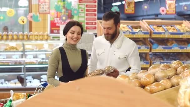 Portrait of a young couple in supermarket, while choosing fresh bread.