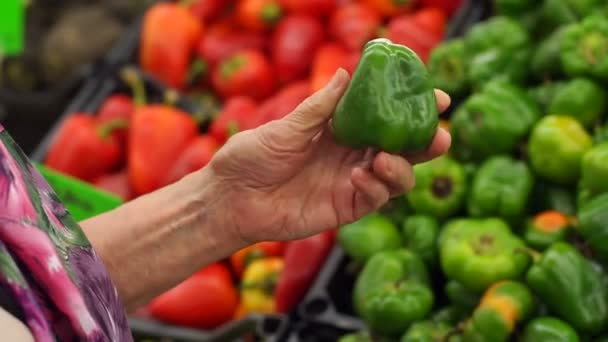 Blízký ruka staré ženy držící v supermarketu zelený pepř.