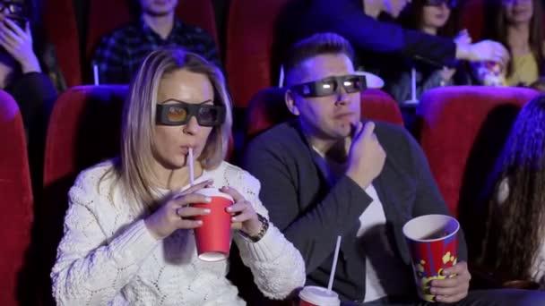 glückliches Paar sitzt im Kino, sieht 3D-Film, isst Popcorn, lächelt