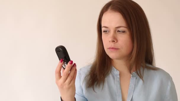 A diabetic girl is holding a blood glucose meter with a high blood sugar level.