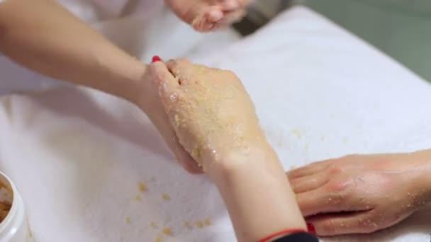 Žena ruce přijímá peeling rukou peelingu kosmetička v salonu krásy.