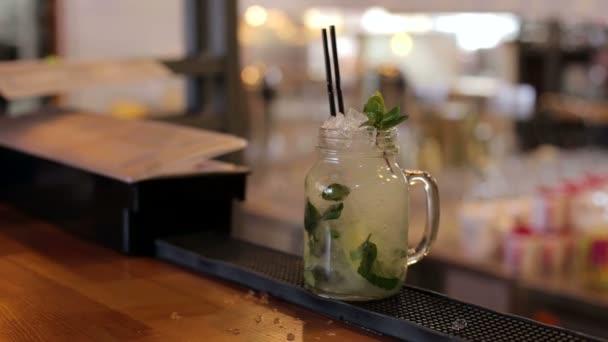 Nahaufnahme von Barkeeper, der Mojito-Cocktails mit Limette, Minze und Rum in der Bar zubereitet.