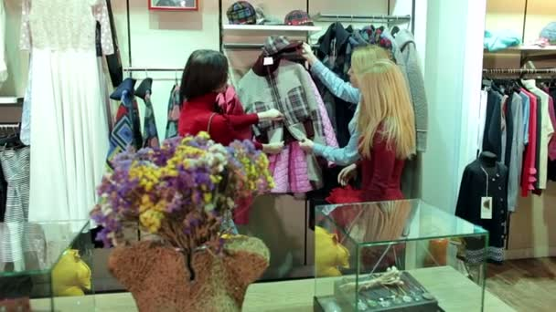 Portrait of three beautiful young women shopping in a clothes shop.