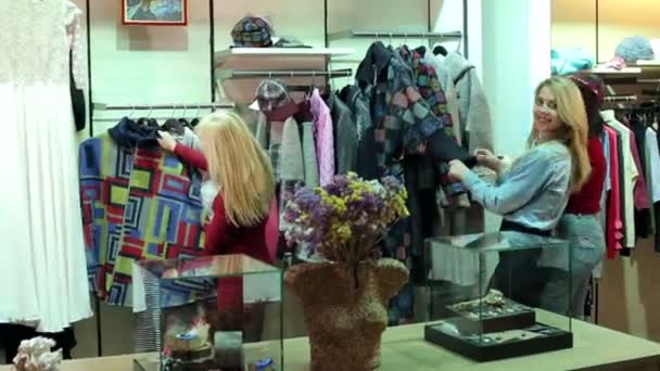 Three girls walk in a clothing store, they look at clothes and try it on.