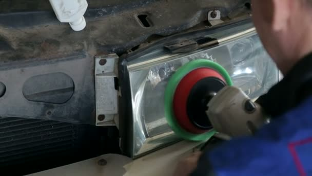Close-up of a mechanic polishes the headlight with a grinding machine.