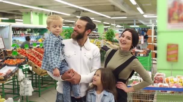 Portrét velké šťastné rodiny se dvěma dětmi v supermarketu.
