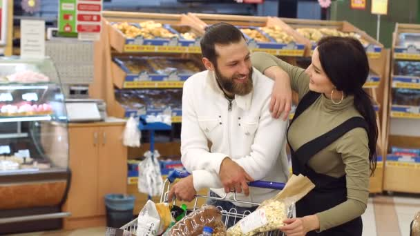 Ritratto di una giovane coppia al supermercato, mentre si sceglie il pane fresco.