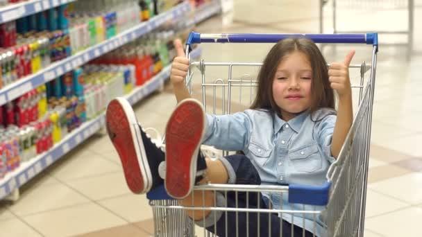 Malá vtipná dívka sedí v obchodě s potravinami v supermarketu a ukazuje palec