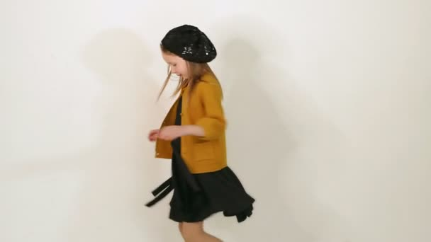 Malá holčička oblečená ve starožitšatech s kloboukem a hnědým svetrem ve studiu