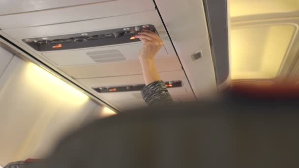 Hand adjusting air conditioning in aircraft cabin.