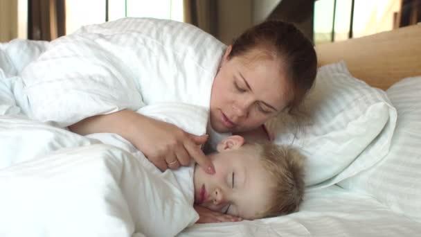 Dítě spí. Máma probudí dítě na posteli v ložnici.