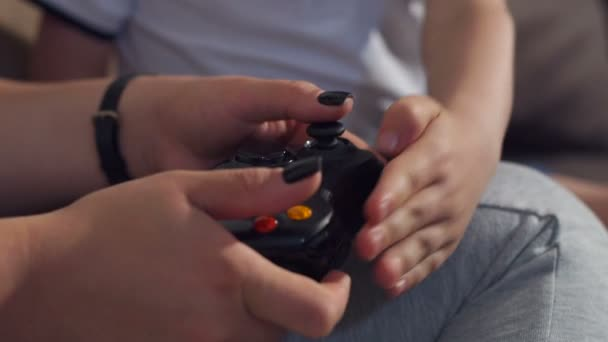 Closeup of a girl with a child playing video games with joysticks in their hands
