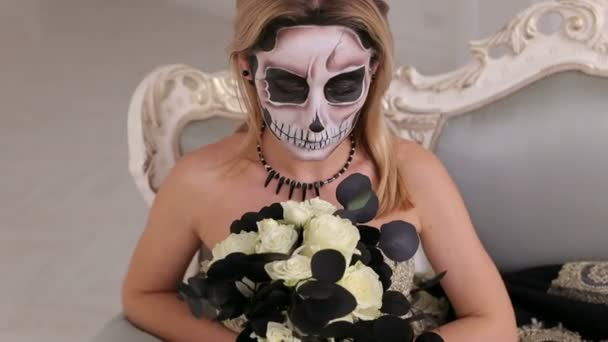 Porträt der Frau mit schrecklichen Halloween Skelett Make-up sitzt auf einem Sofa.