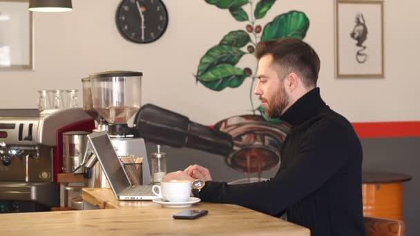 Portré egy fiatal szakállas üzletember egy kávézóban, dolgozik a laptop