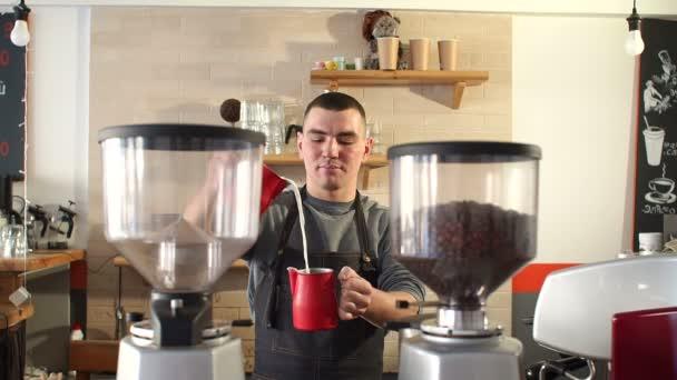 Egy férfi működik, mint egy Barista egy kávézóban, aki Önt tejet egy csésze kávét.