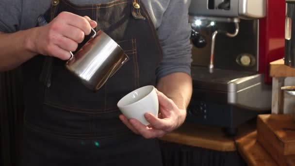 Professional barista pouring steamed milk into coffee cup making latte art.